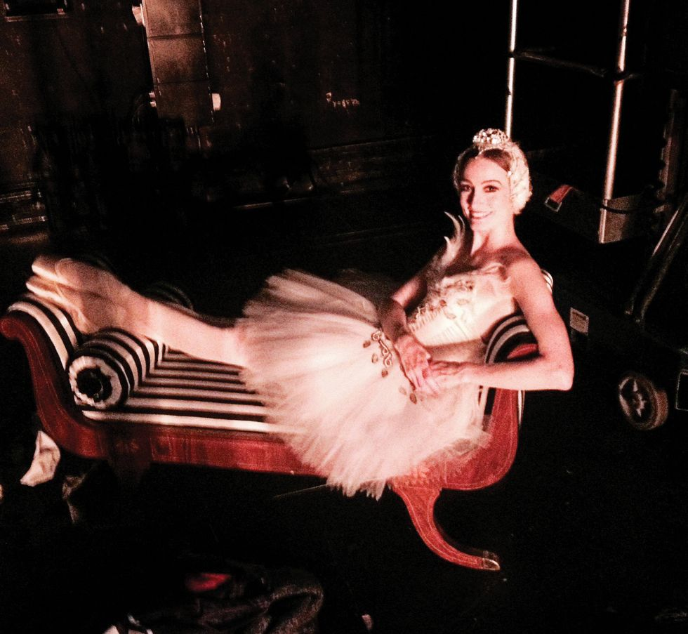 A grainy photograph of Julie Kent in a white swan tutu and headpiece, lounging on a striped chaise lounge with her hands on one hip and her feet crossed at the ankle.