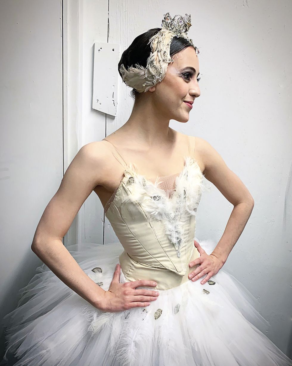 Barkman stands backstage in a white swan tutu and headpiece with her hands on her hips.