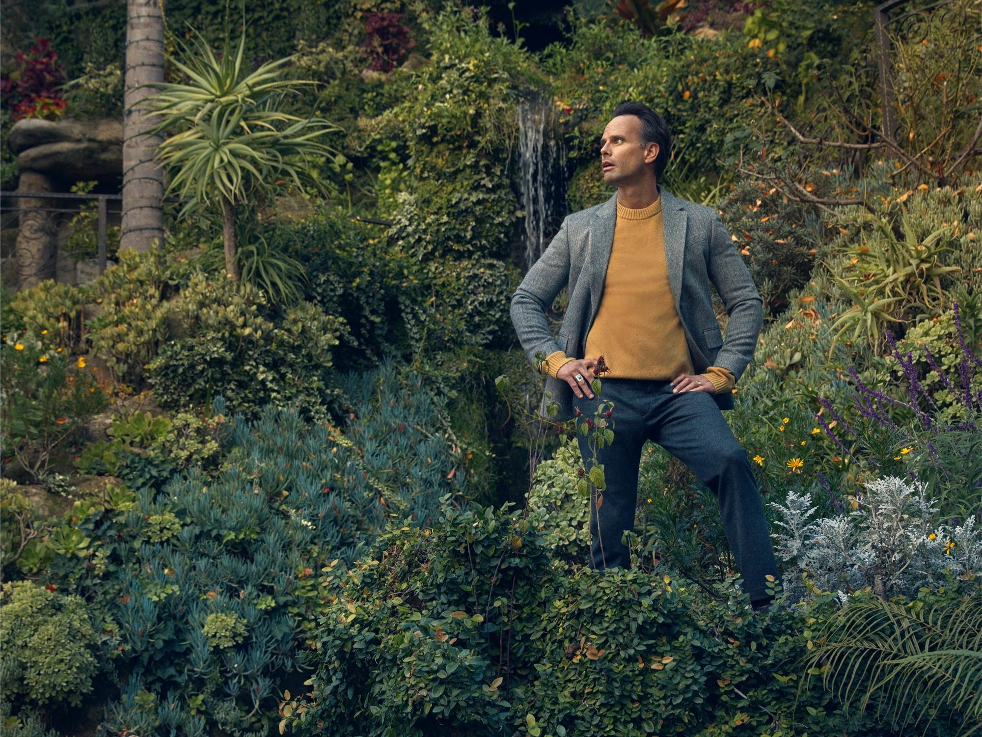 Walton Goggins standing in a beautiful landscaped garden.
