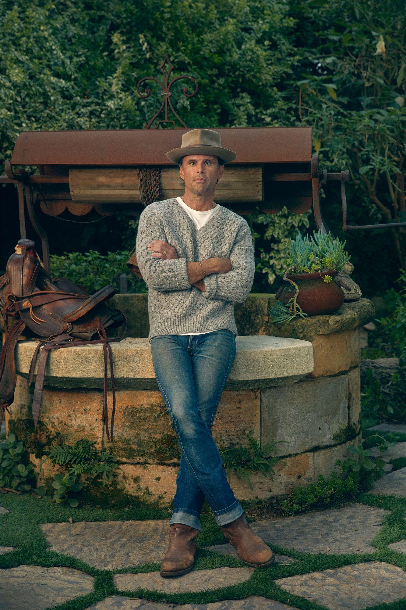 Walton Goggins leaning against a well.