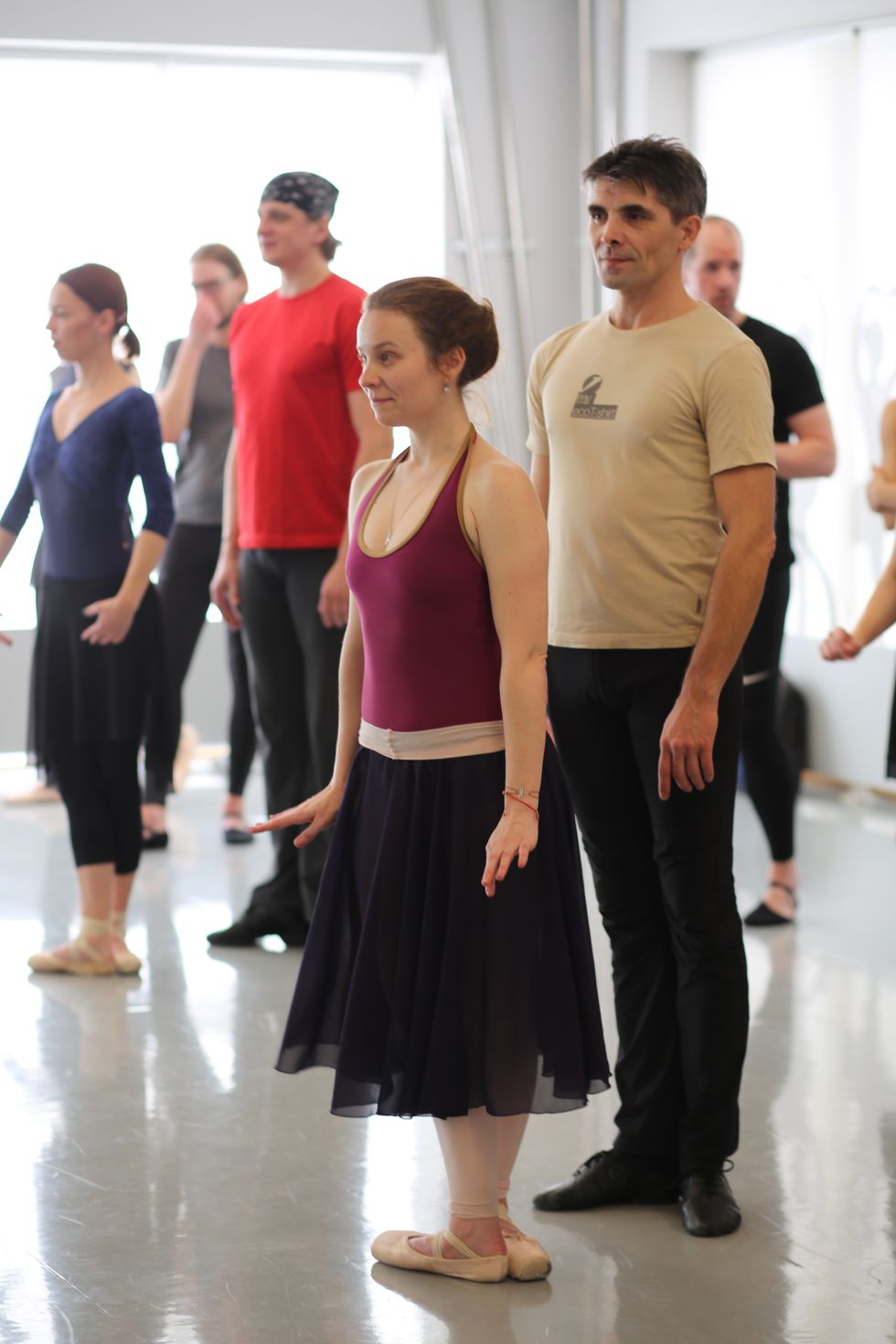During a pas de deux class, a woman in a burgundy leotard, black skirt and pointe shoes stands in fifth position while her partner, in a beige T-shirt and black pants, stands behind her in a loose first position.