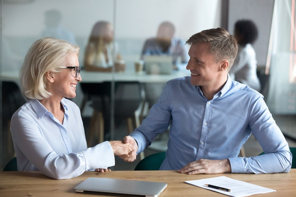Professional man receives advice about career success from an older co-worker