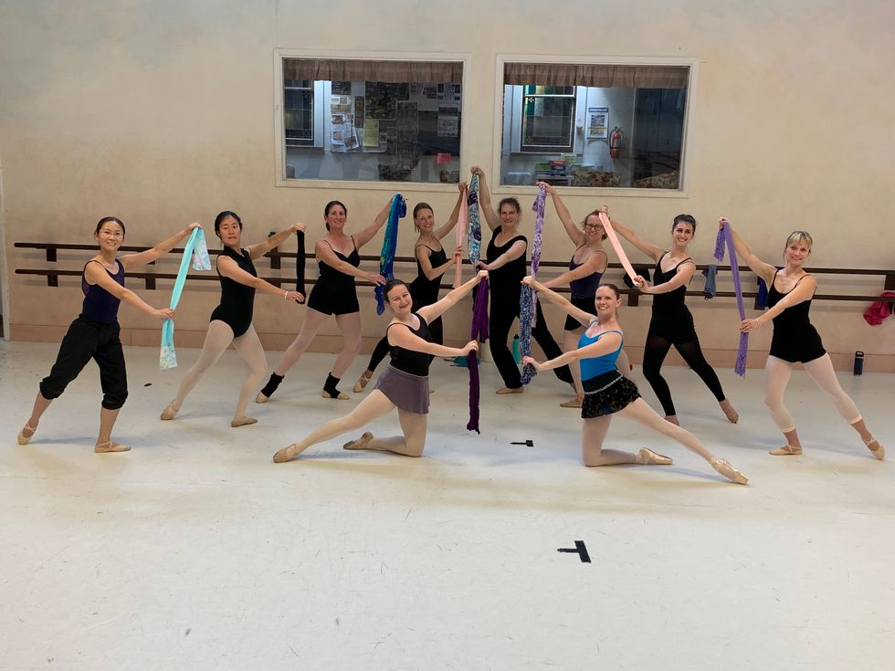 A group of 8 women lunge in tendu back with their arms in third position, holding a long scarf. Two other women kneel on the ground in a similar position with thier back leg and amrs. They all wear dark leotards, tights and some wear short skirts and warm-up pants.