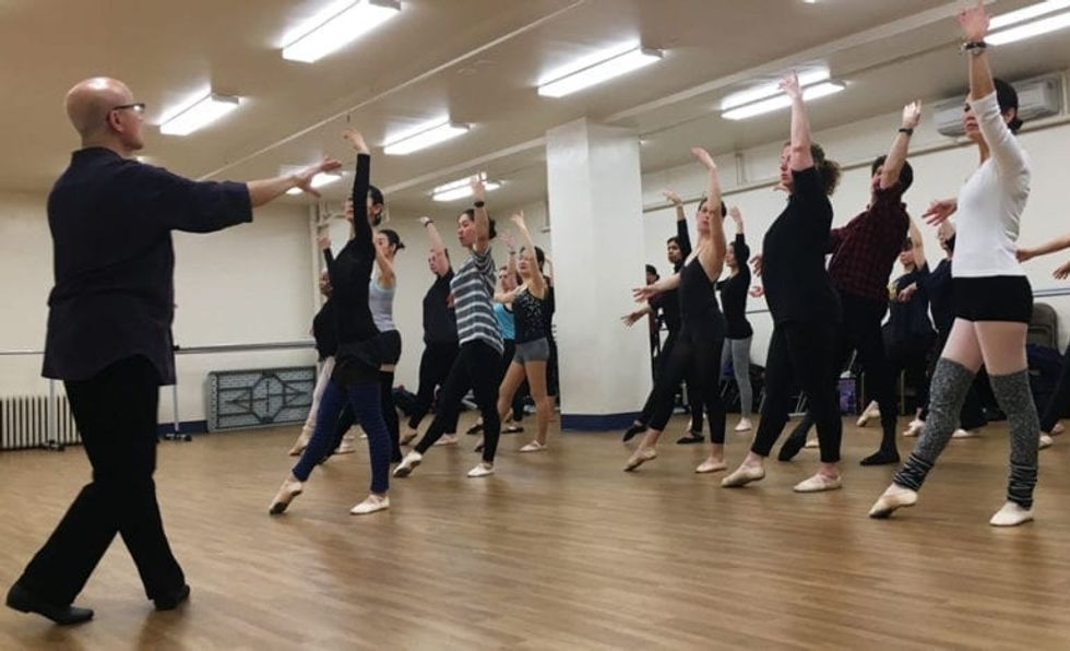 Finis Jhung, wearing black pants, a black shirt and glasses, speaks to a large group of adult students as they execute a tendu combination in center.