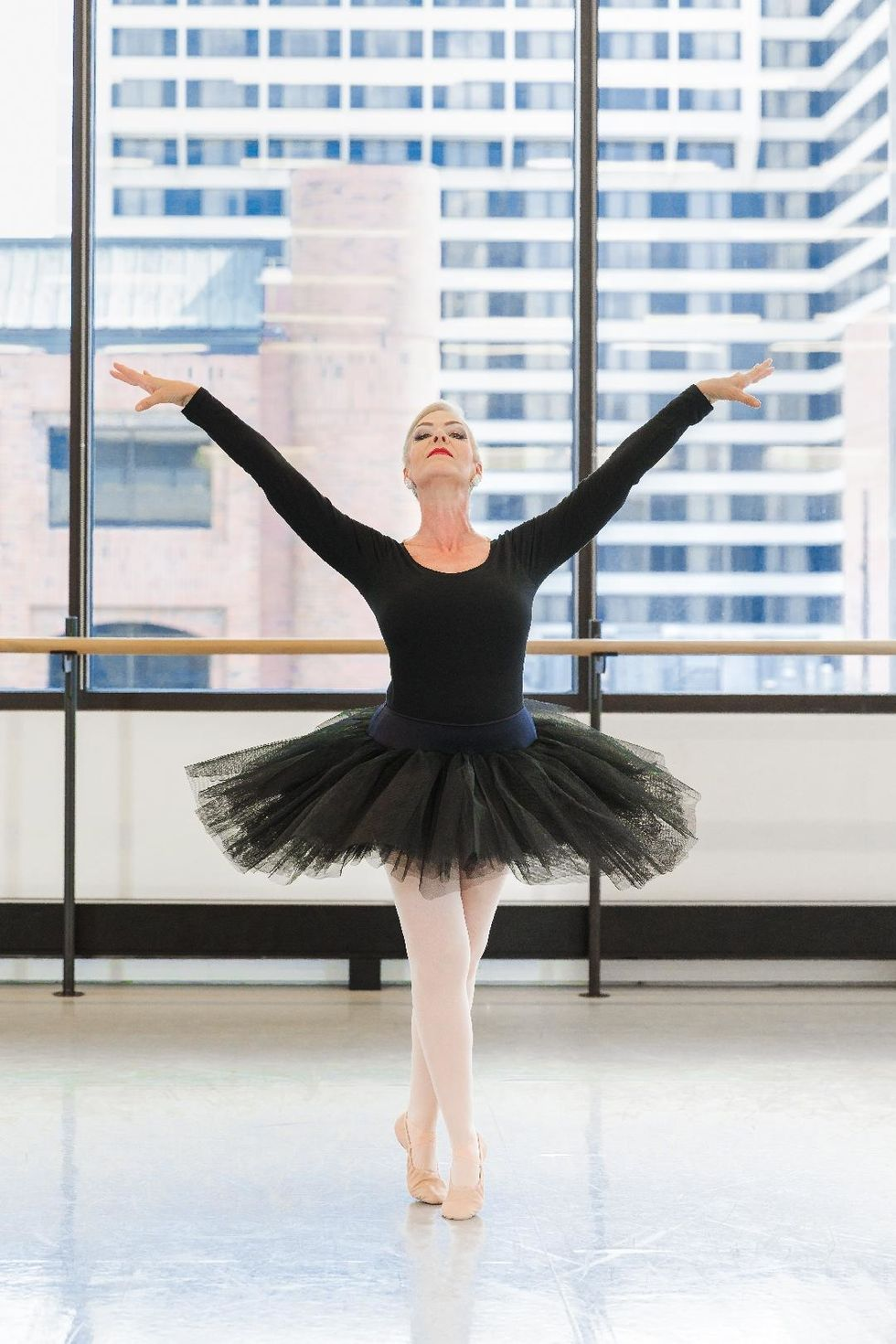 A middle aged woman in a long-sleeved black leotard, black tutu, pink tights and ballet slipper, poses dramatically in sus-sous, her arms in a V shape.