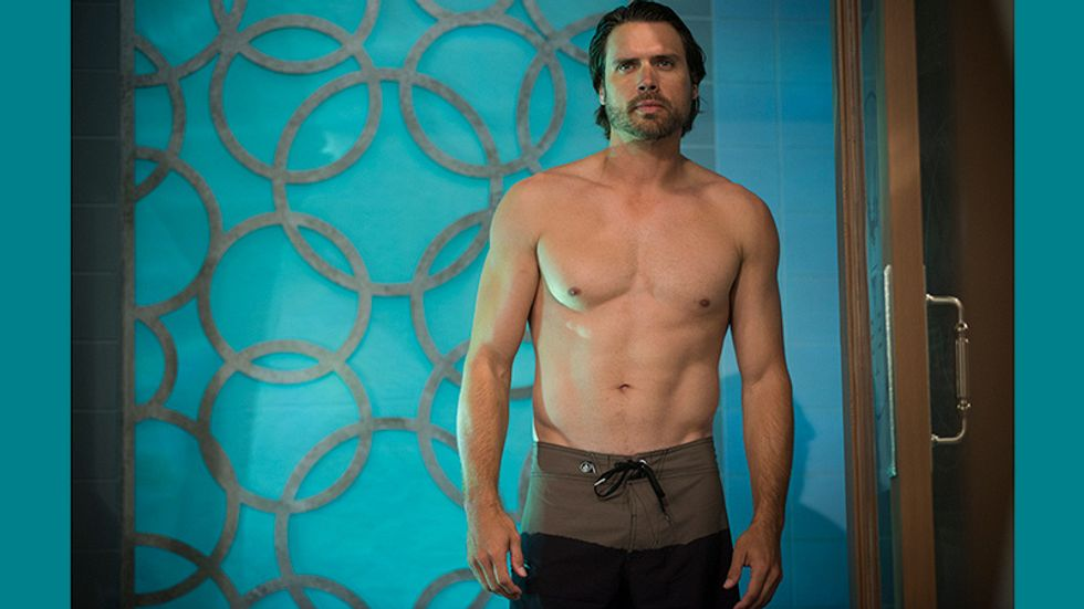 Joshua Morrow poses shirtless against a patterned blue wall.