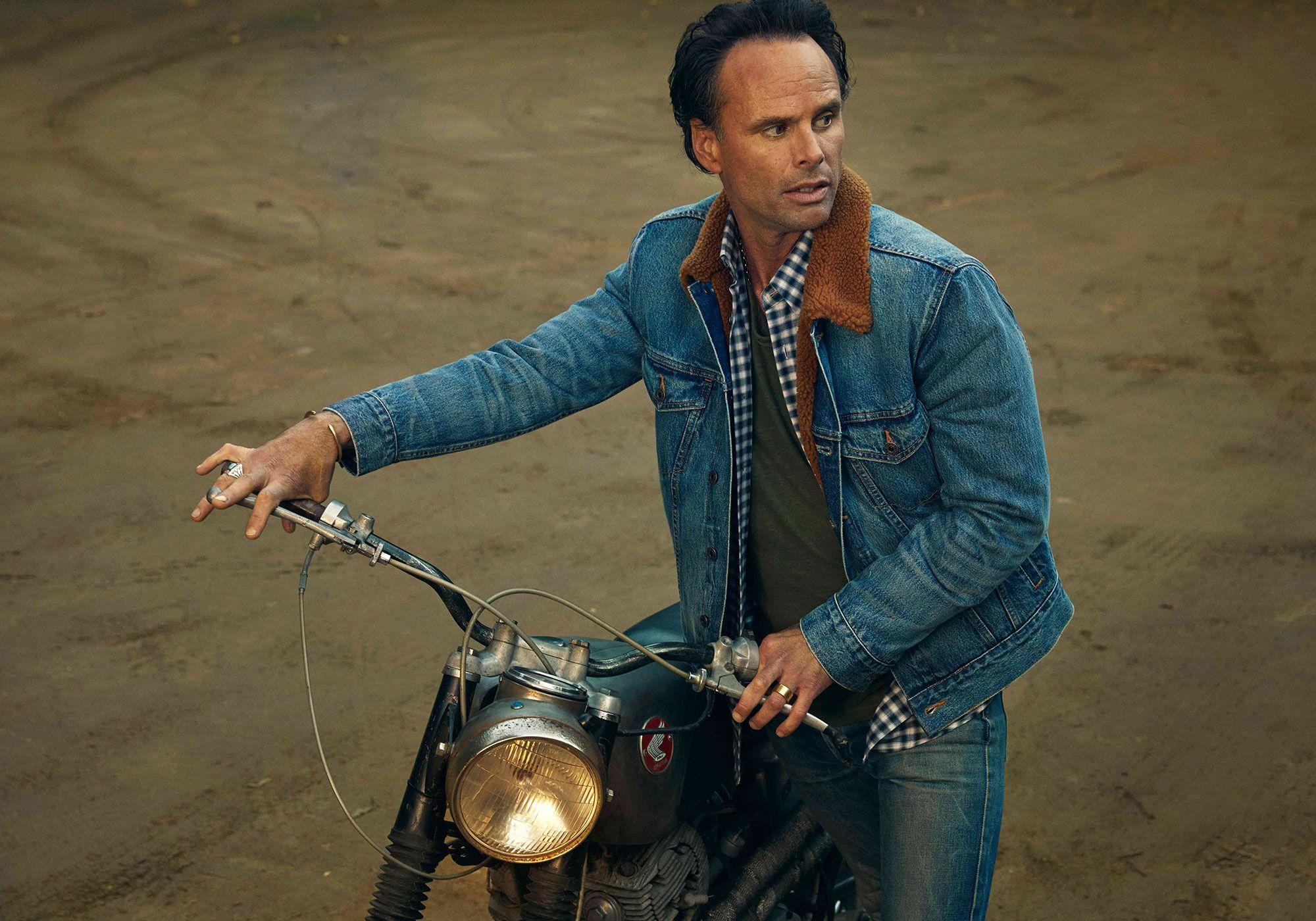 Walton Goggins wearing denim and riding a motorcycle.