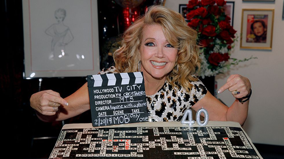 Melody Thomas Scott kneeling next to and pointing at her cake