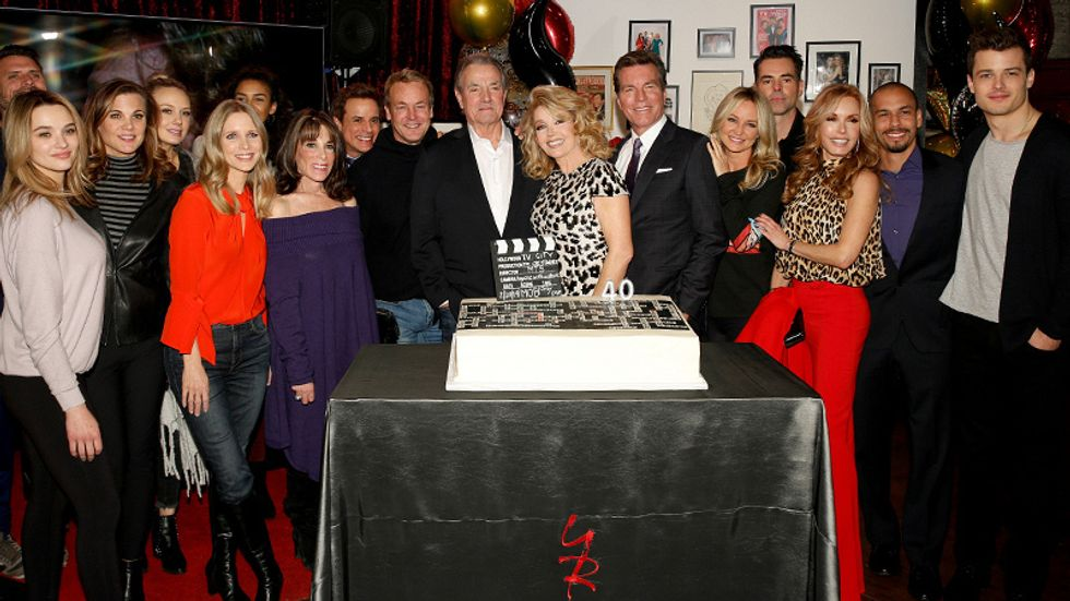 Melody Thomas Scott with a crowd of friends in family in front of her celebratory cake
