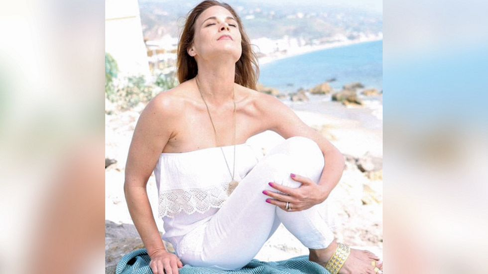 Gina Tognoni in a white outfit basking in the sun.