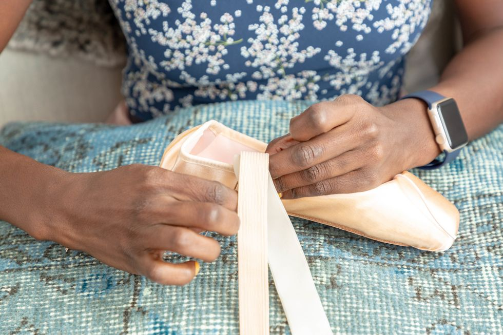 Close-up of hands sewing a pointe shoe.