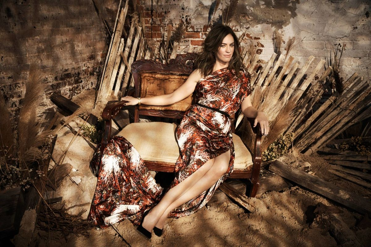 Maggie Siff sitting on a throne-like seat.