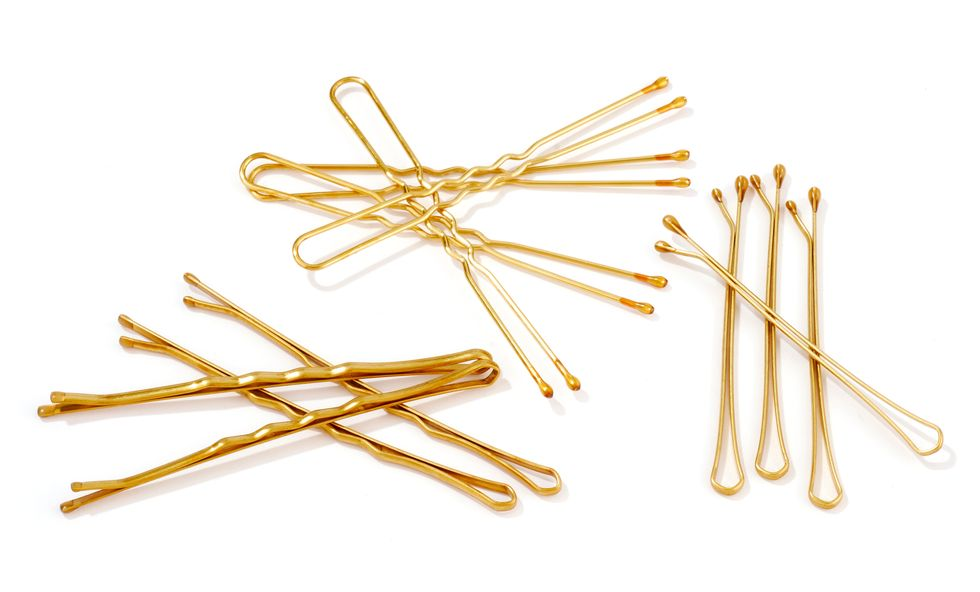 Gold bobby pins against a white background.
