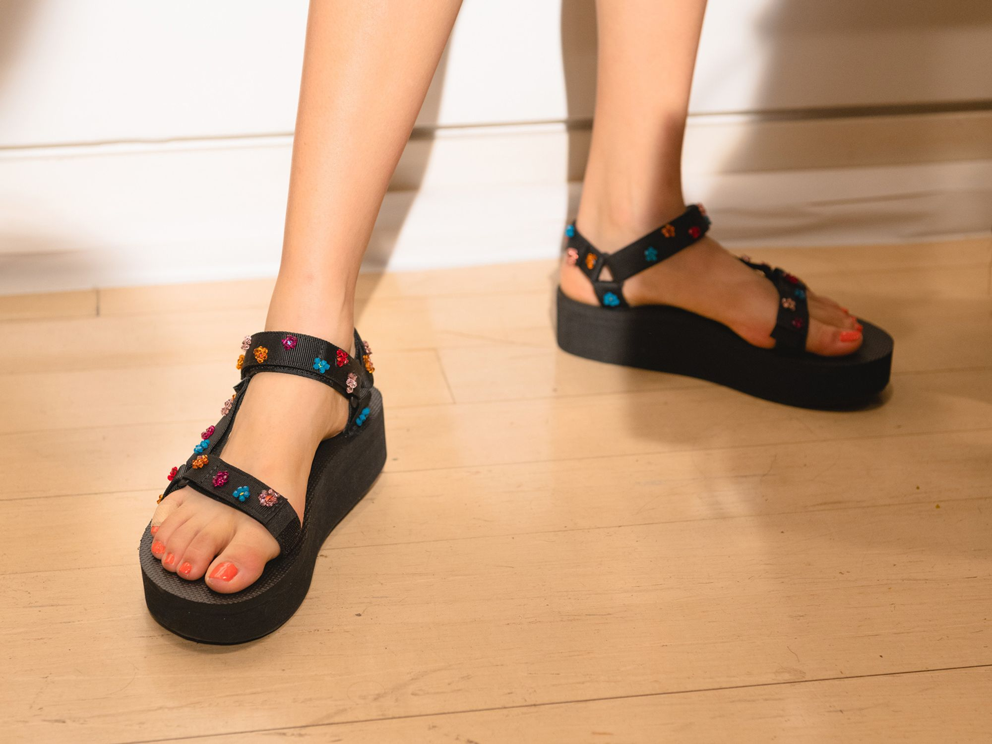 Bedazzled Teva shoes on a foot model.