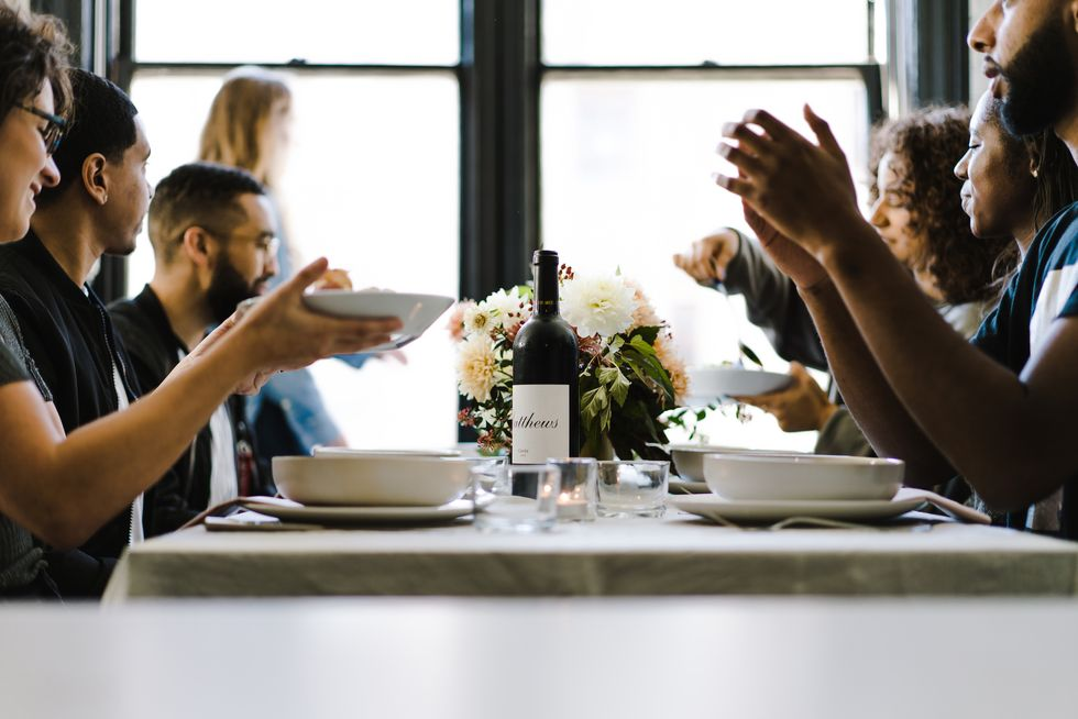 People of color at a long table having a dinner party.