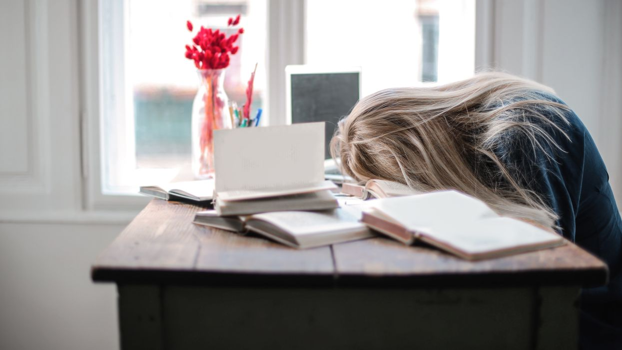 woman sleeping on books at her desk