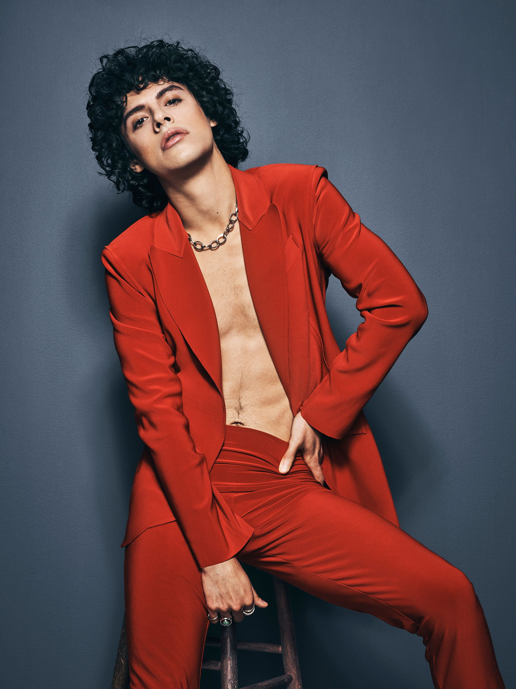 Jonny Beauchamp in a red suit with no shirt.