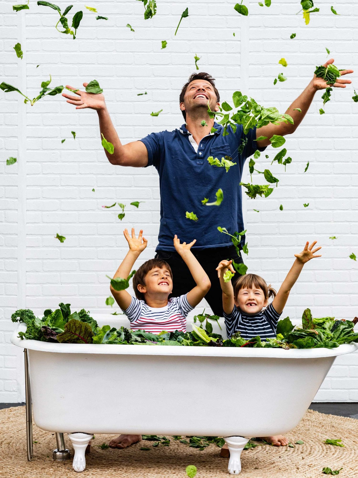 Misha Collins and kids tossing lettuce leaves in the air.