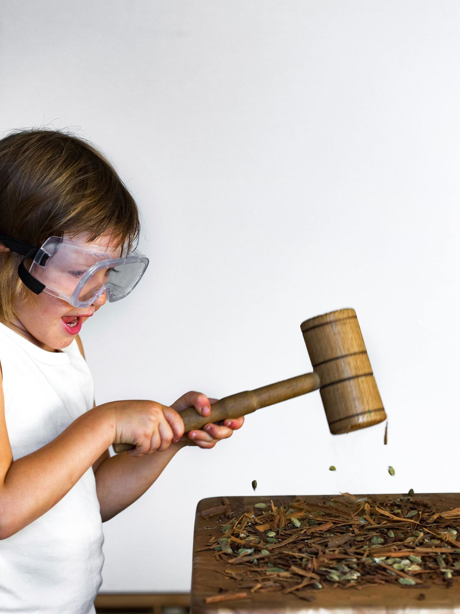 Child smashing herbs with a cooking mallet.