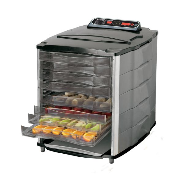 Food dehydrator with trays of fresh fruit slices.