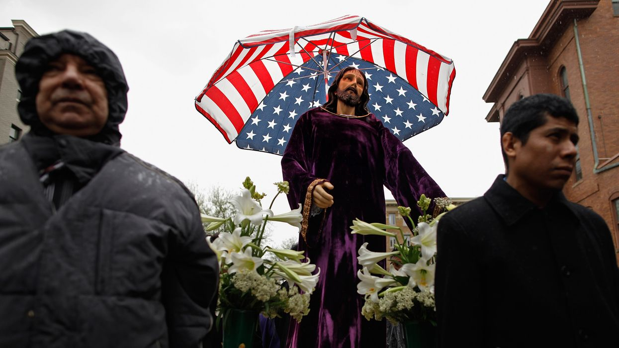 Statue of Jesus Christ wearing a robe under an American flag umbrella