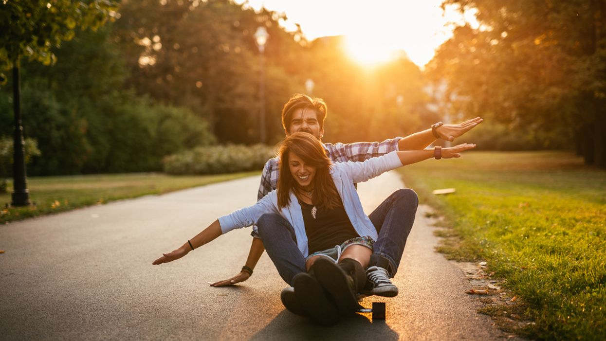 couple in love smiling on a skateboard at sunset