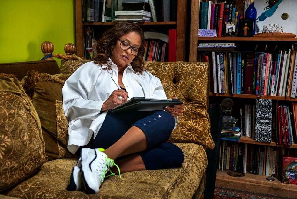 Debbie Allen sits on a couch in her office, her legs tucked beneath her as she works on a tablet