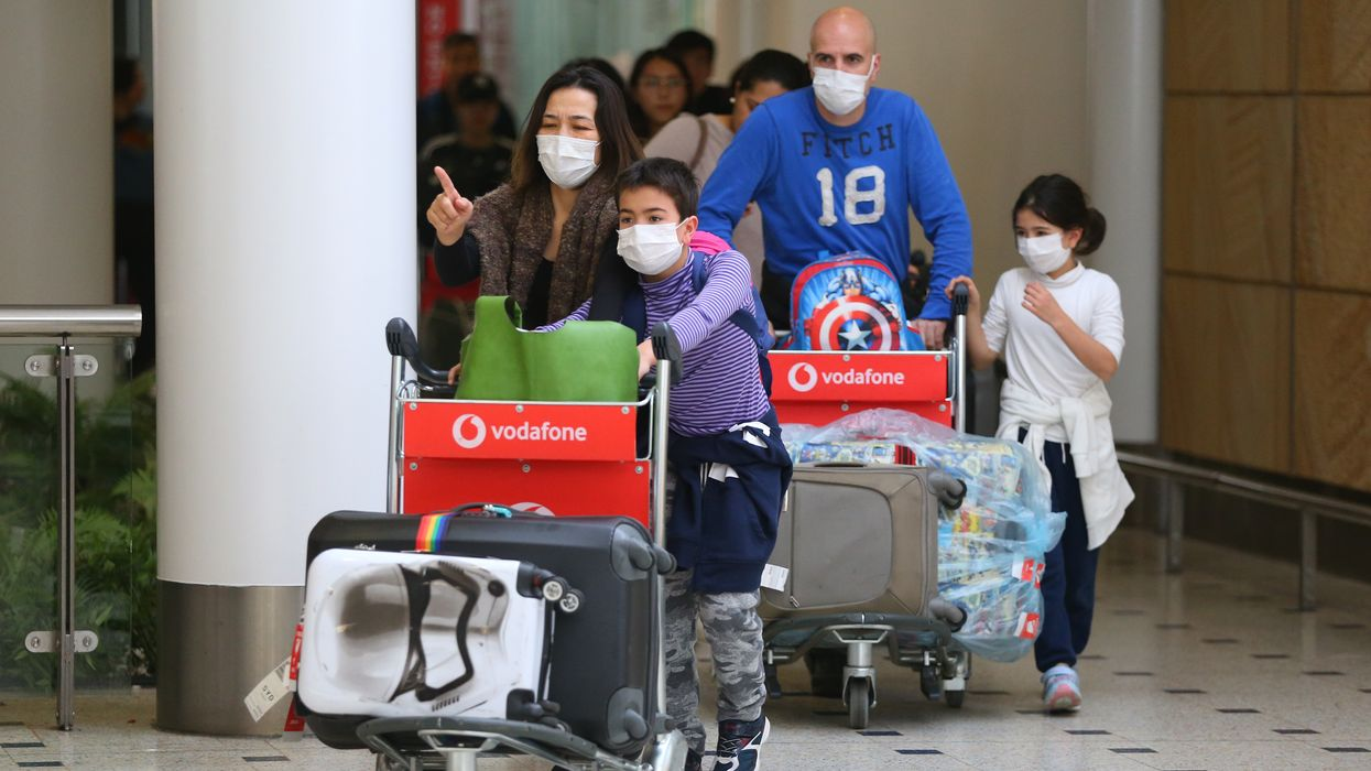 Travelers at an airport wearing facemasks