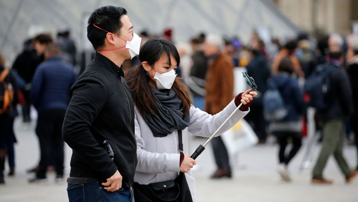 A couple wearing protective masks at the Louvre with a selfie stick