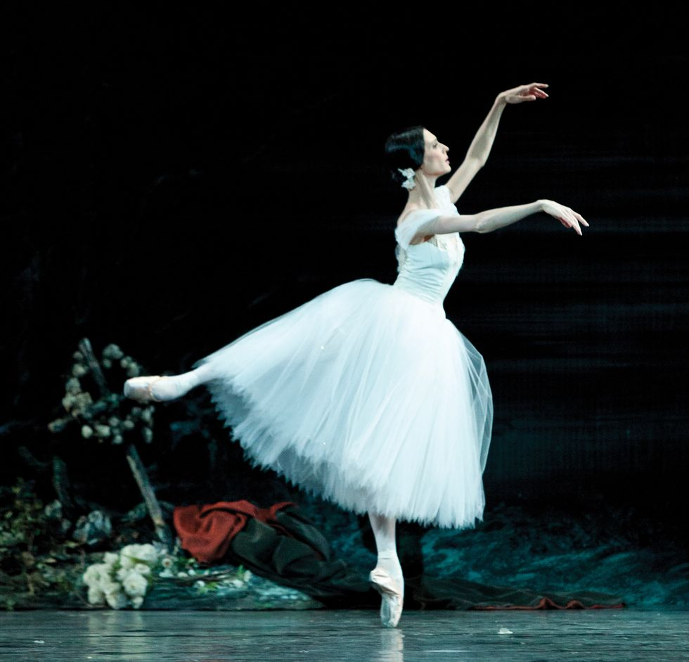 Hodgkinson, in a white tutu, in an arabesque on pointe with her arms in fourth position.