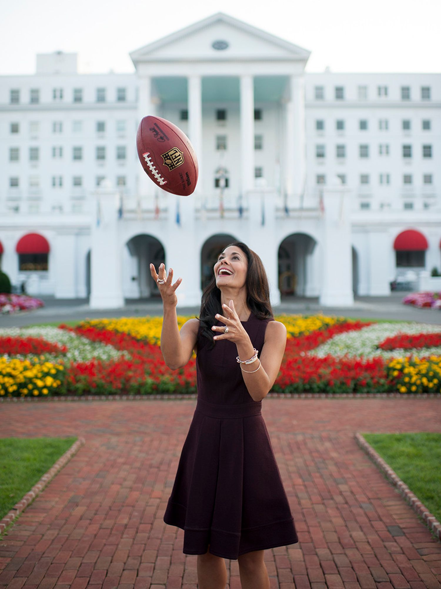 Tracy Wolfson tossing a football up in the air.