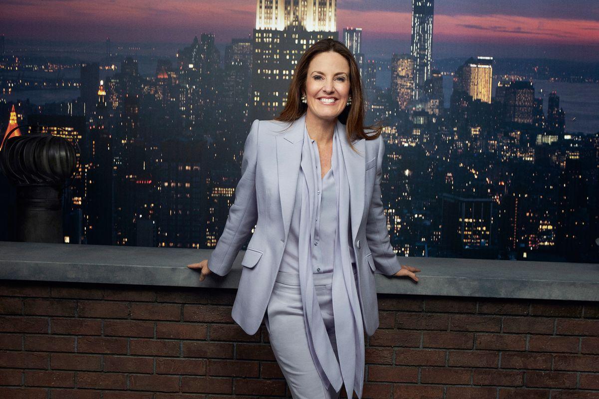 Sharyn Alfonsi posing in front of a Manhattan skyline backdrop.