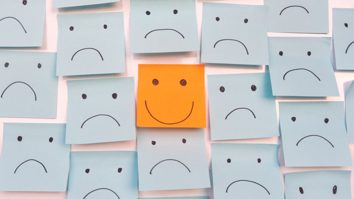 concept of happiness and self-confidence smiley face sticky note with sad face sticky notes