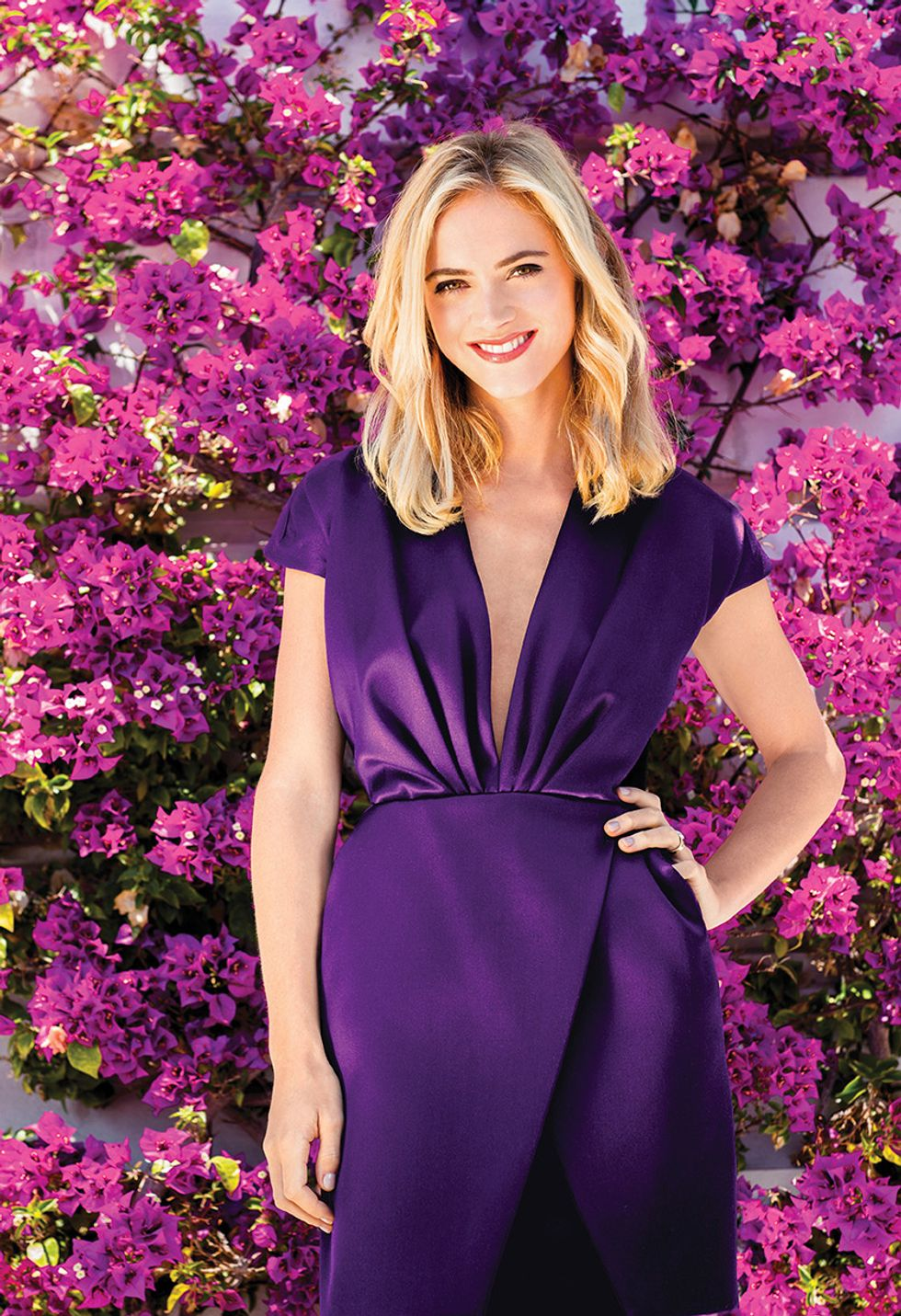 Emily Wickersham of NCIS in violet dress in front of flowers.
