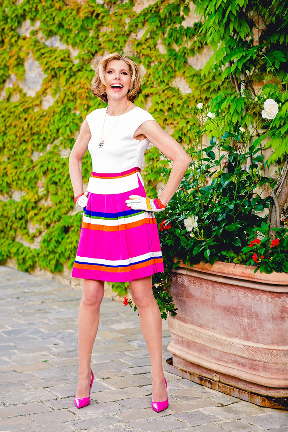 Christine Baranski of The Good Fight in a pink striped skirt and pink heels.
