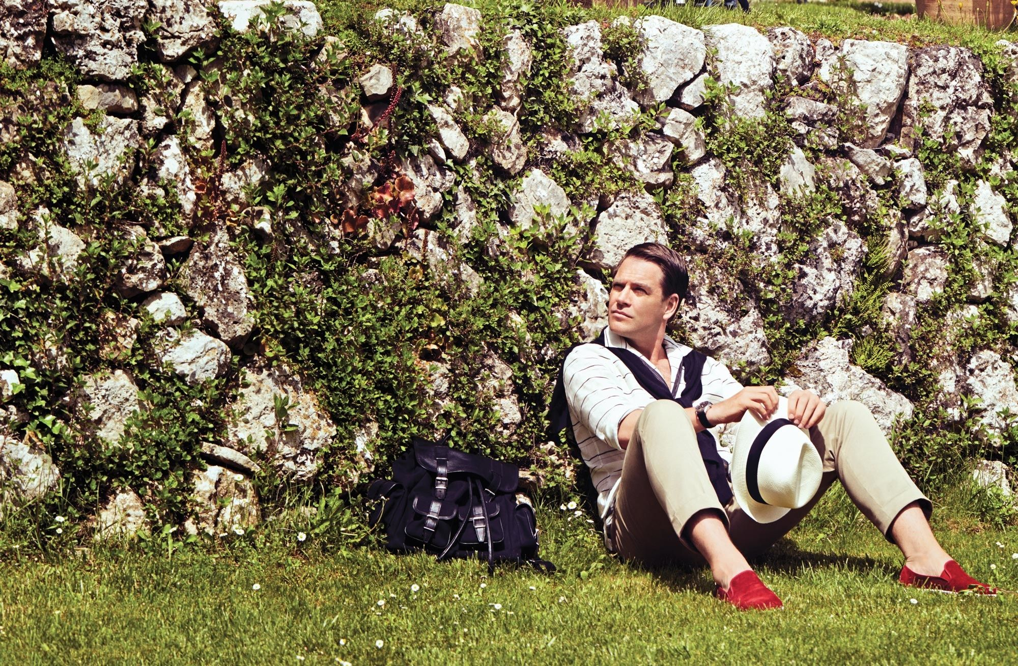 Michael Weatherly of Bull with red shoes sitting on grass