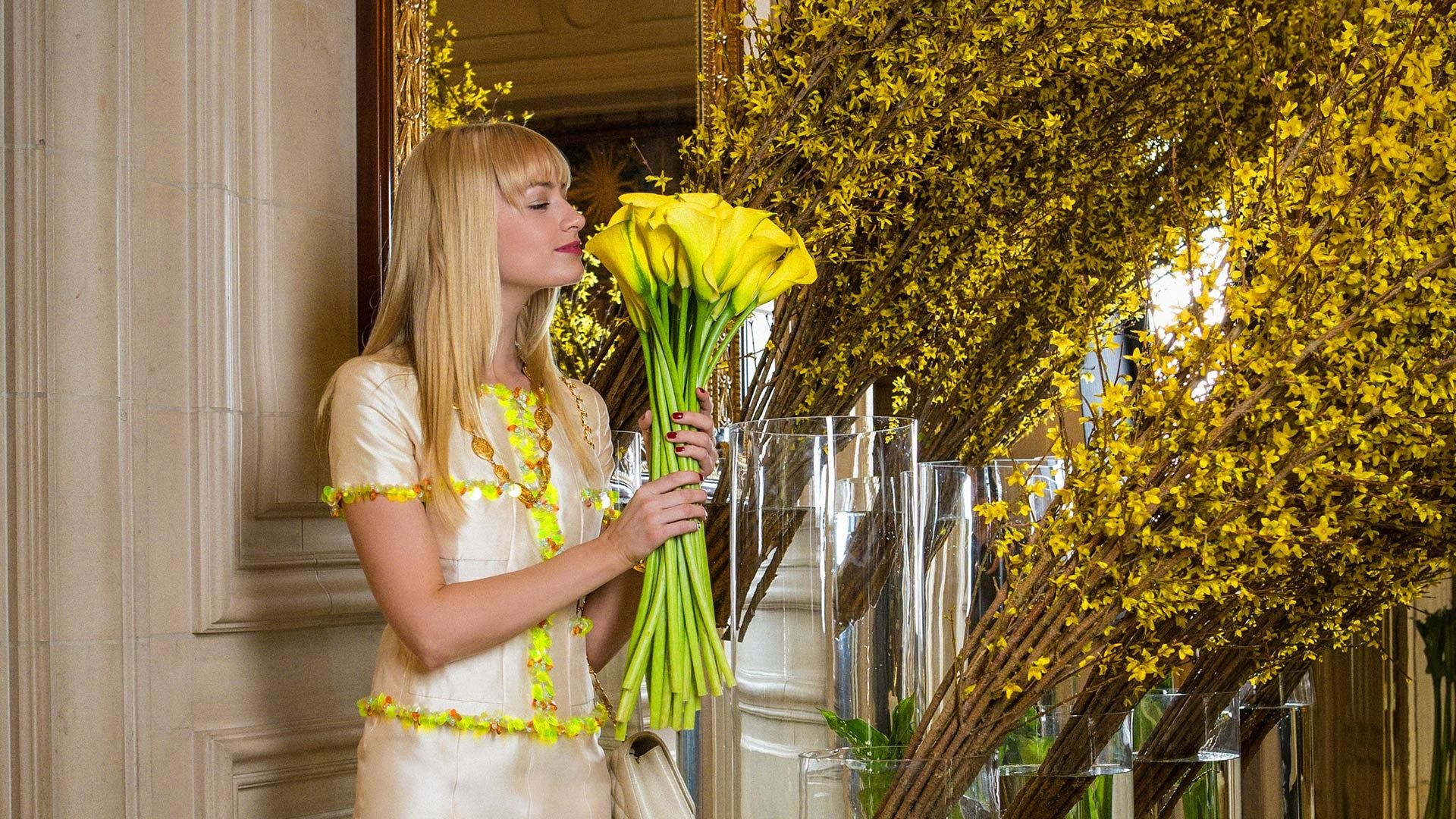 Beth Behrs smelling yellow calla lilies.