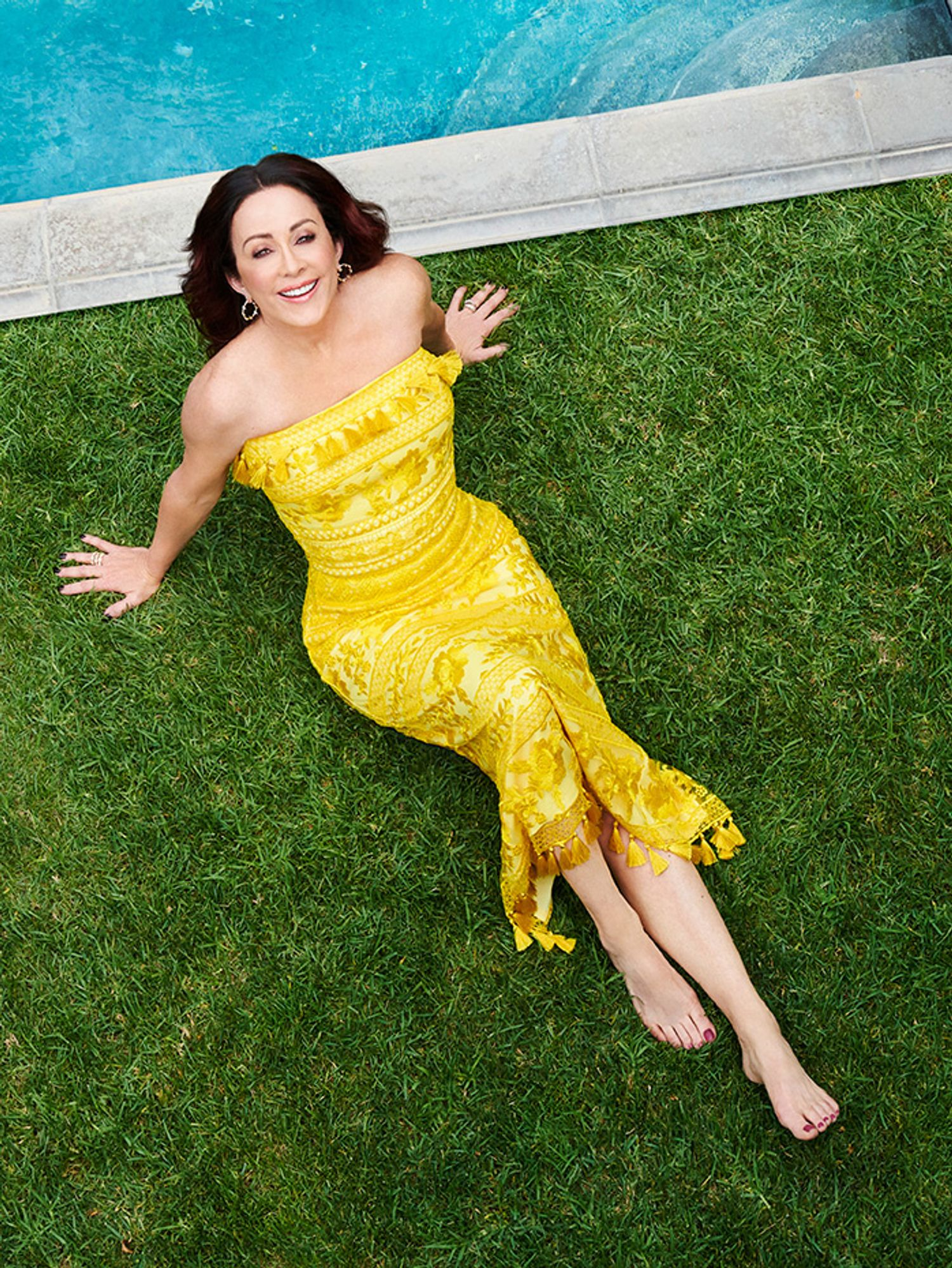 Patricia Heaton sitting on grass in a yellow dress.