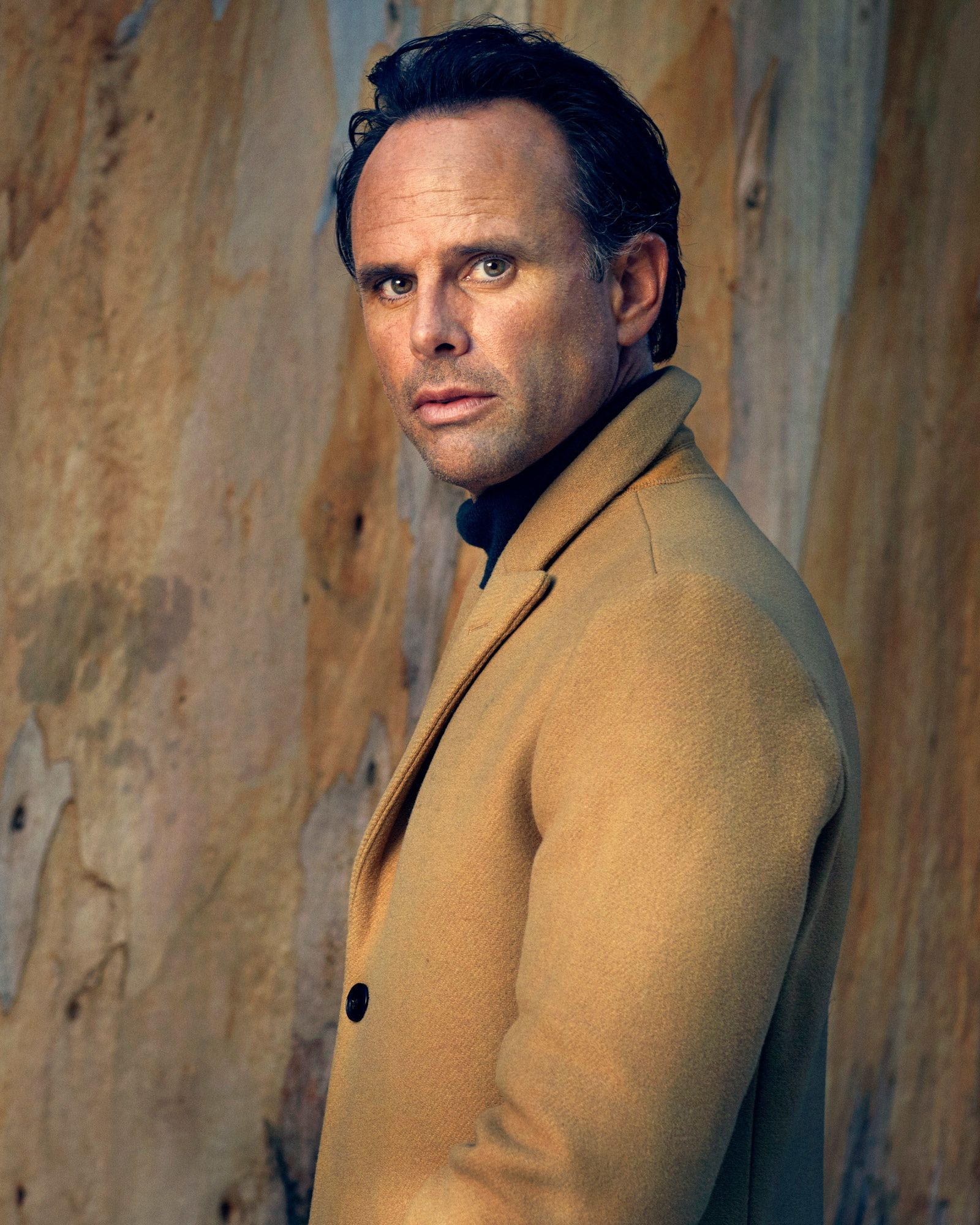 Walton Goggins looking sideways into the camera wearing a camel coat.