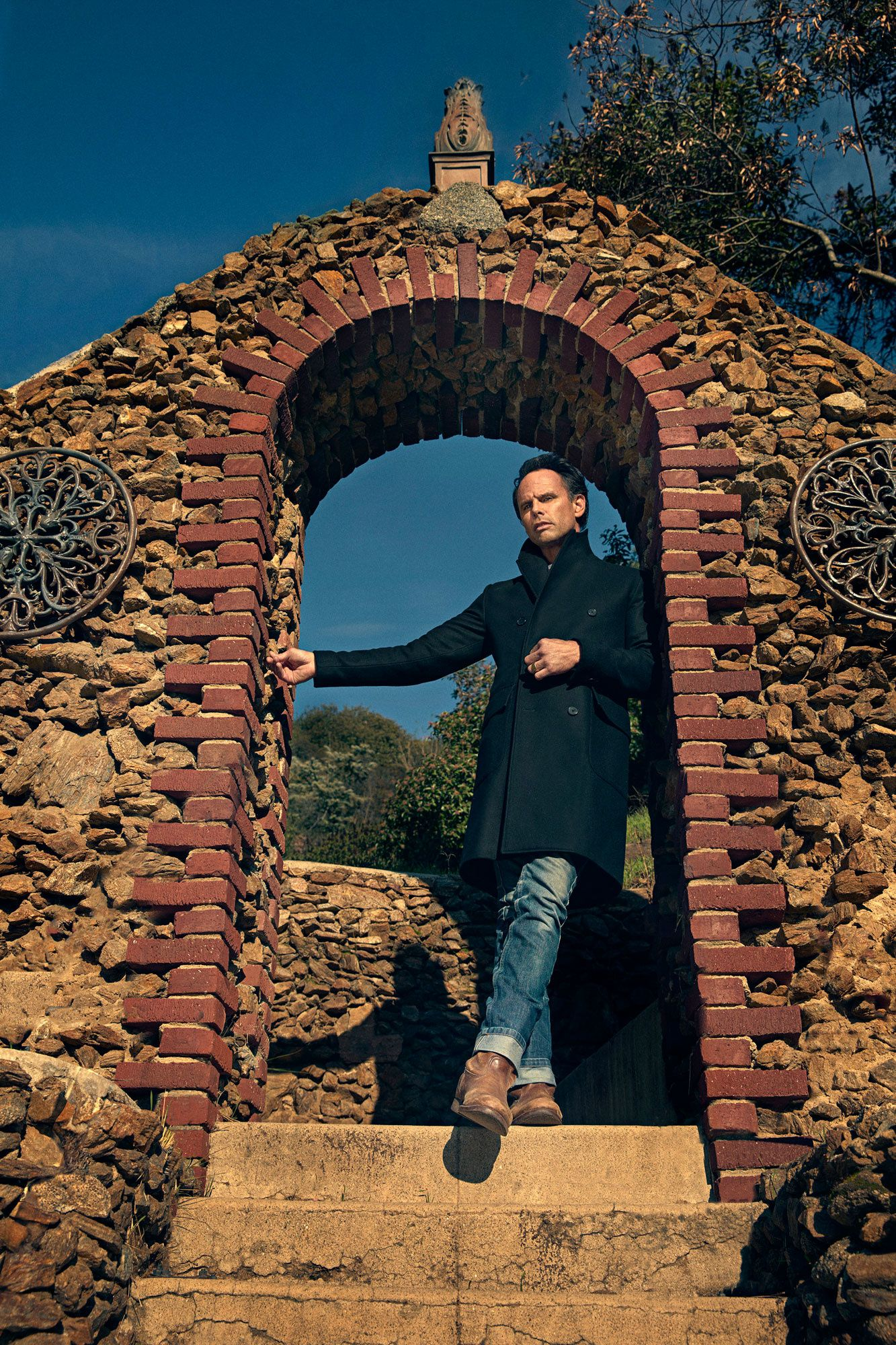 Walton Goggins standing in a stone archway.