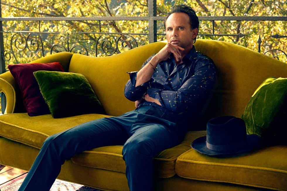 Walton Goggins sitting on a mustard color velvet sofa staring into the camera.