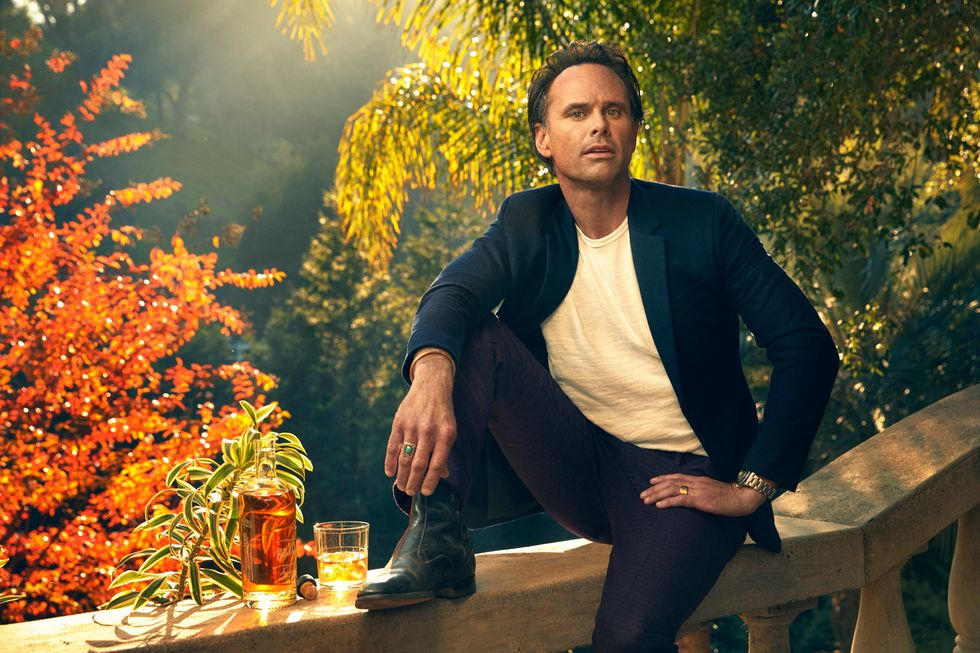 Walton Goggins sitting on a stone balustrade, sun backlit with fall colors, a glass of whiskey beside him.