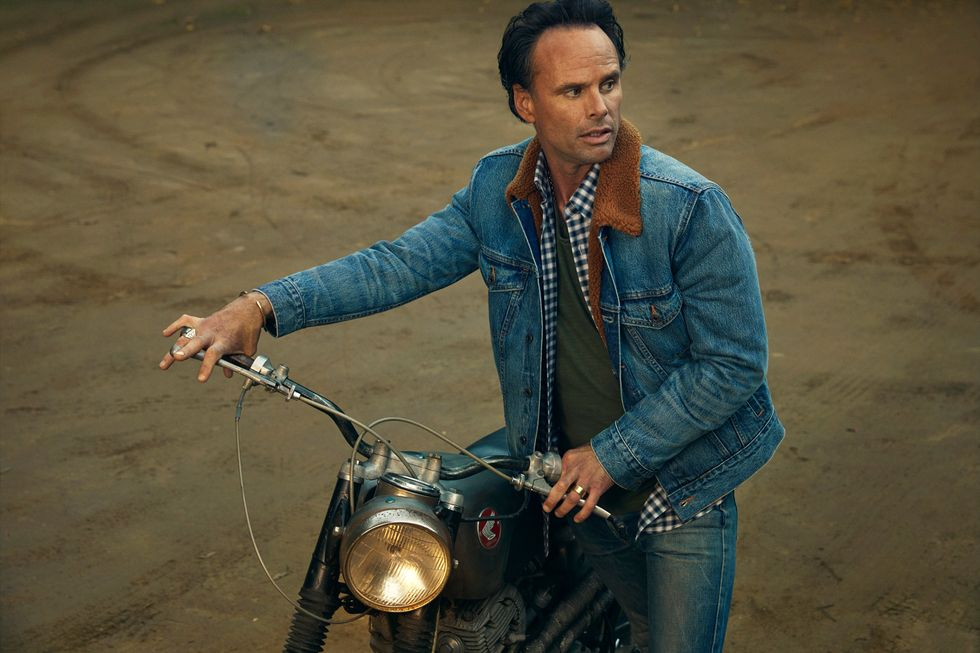 Walton Goggins in a seated pose on a vintage motor cycle, looking sideways.