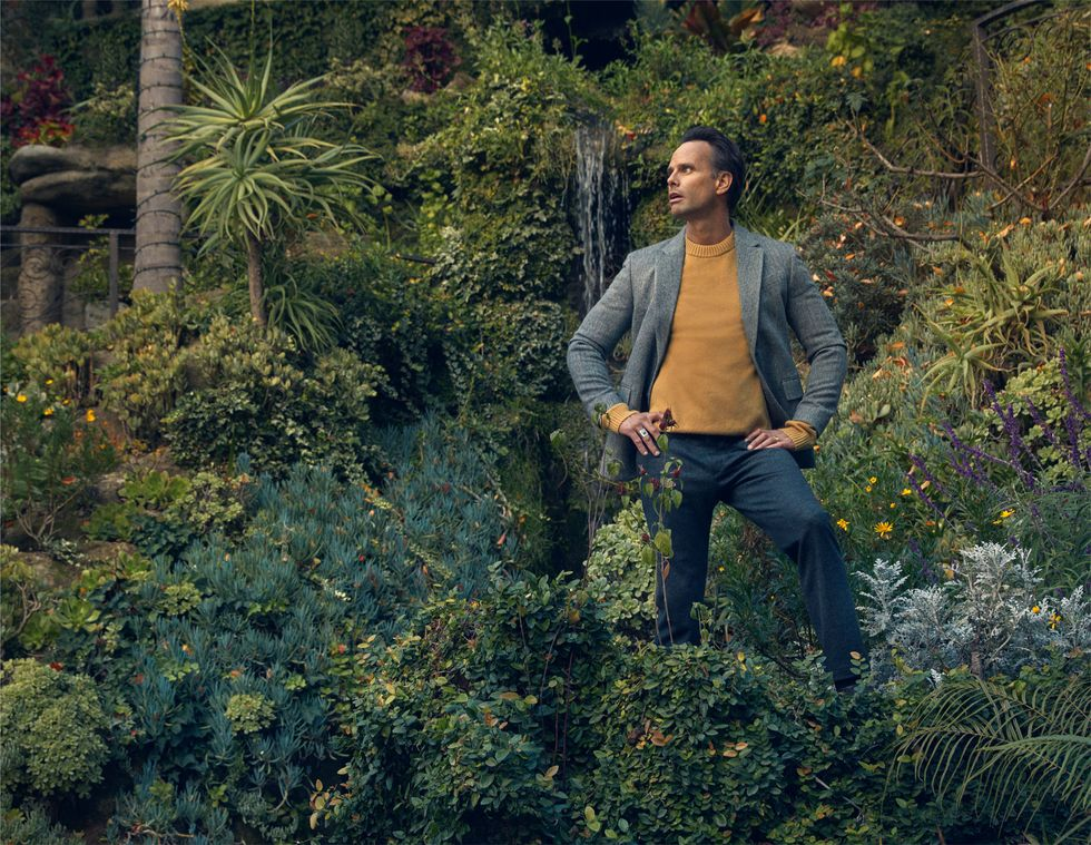 Walton Goggins surrounded by trees and foliage and a small waterfall.