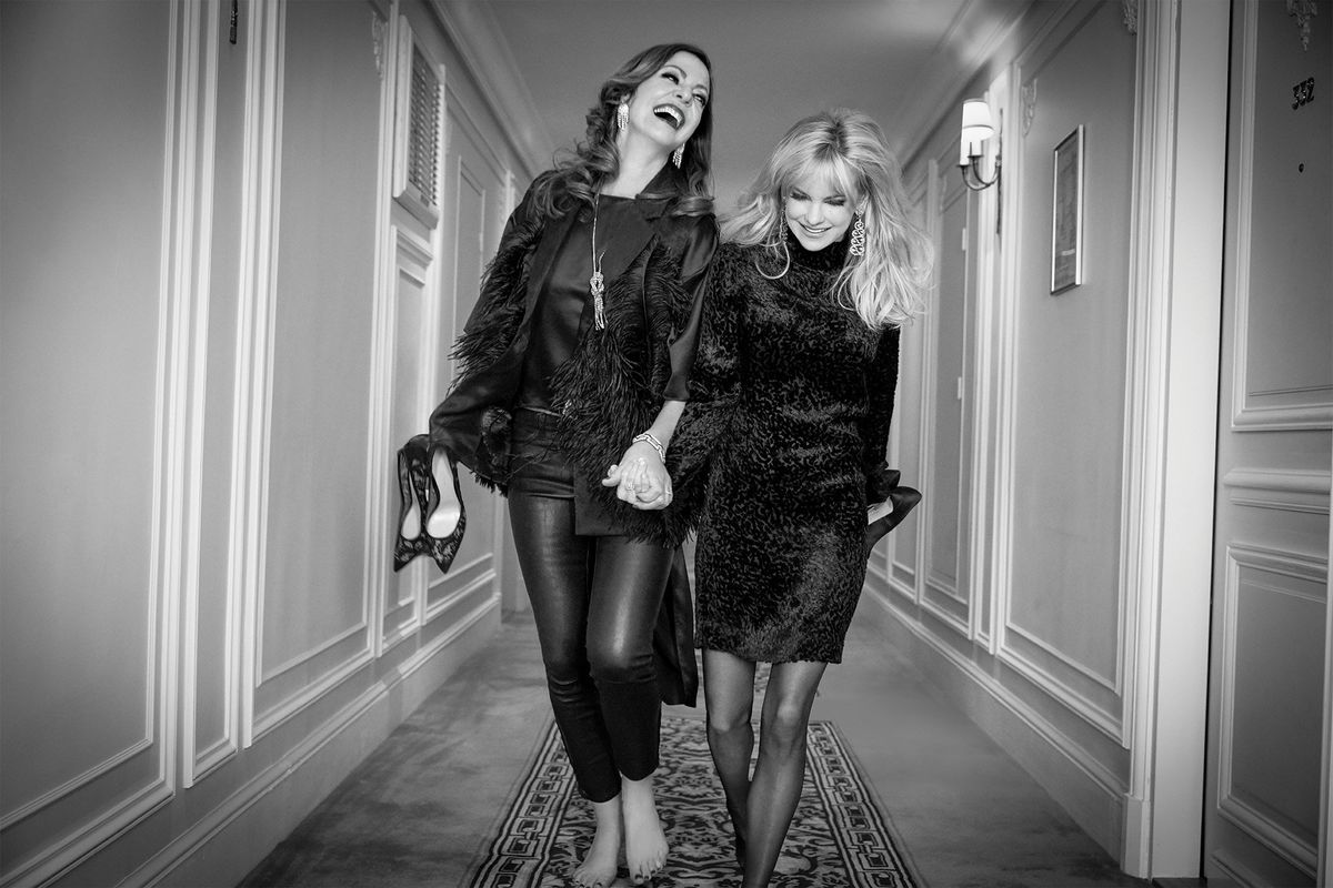 Black and white photo Allison Janney and Anna Faris holding hands.
