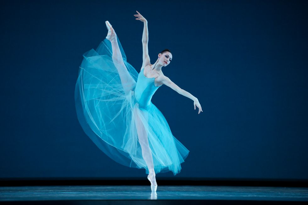 Sylvie, in a long light blue tutu and leotard, stands off-center on pointe with one leg extended high in the air. She looks over her left arm.