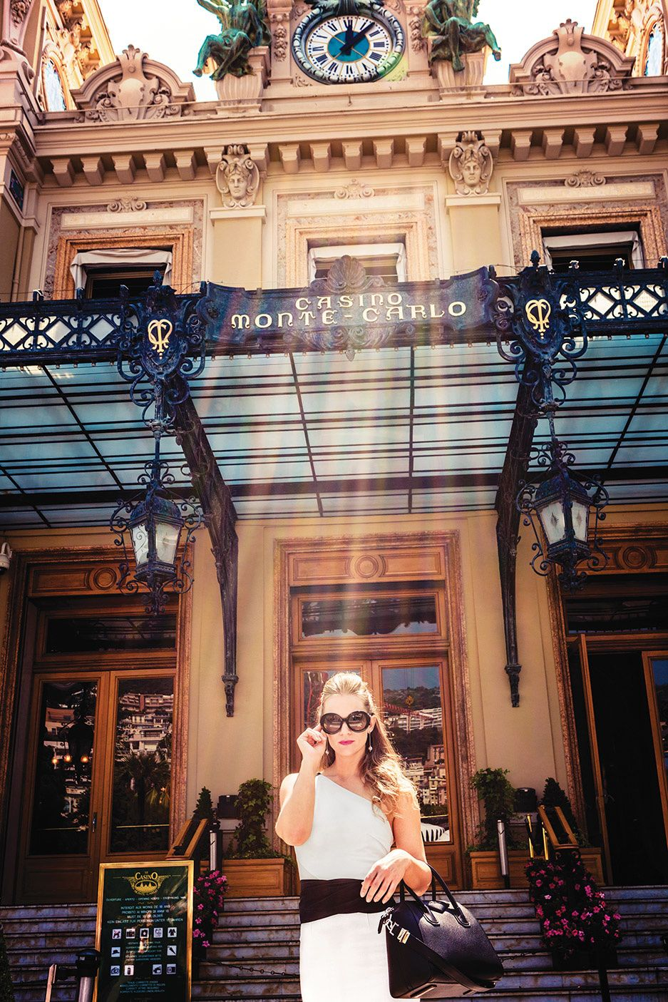 AJ Cook in large sunglasses and a white dress in front of Casino Monte Carlo