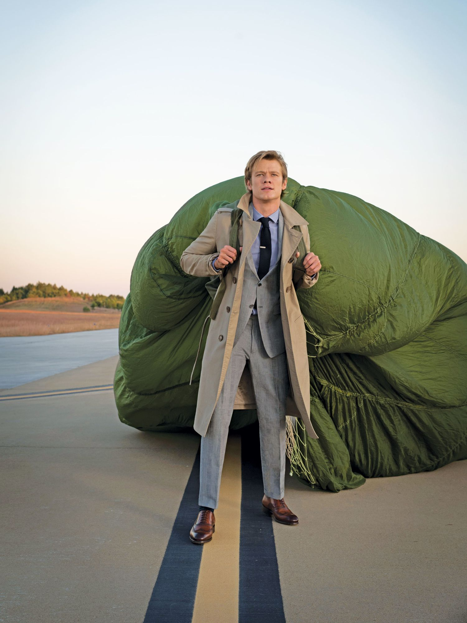 Lucas Till in a gray suit and camel jacket