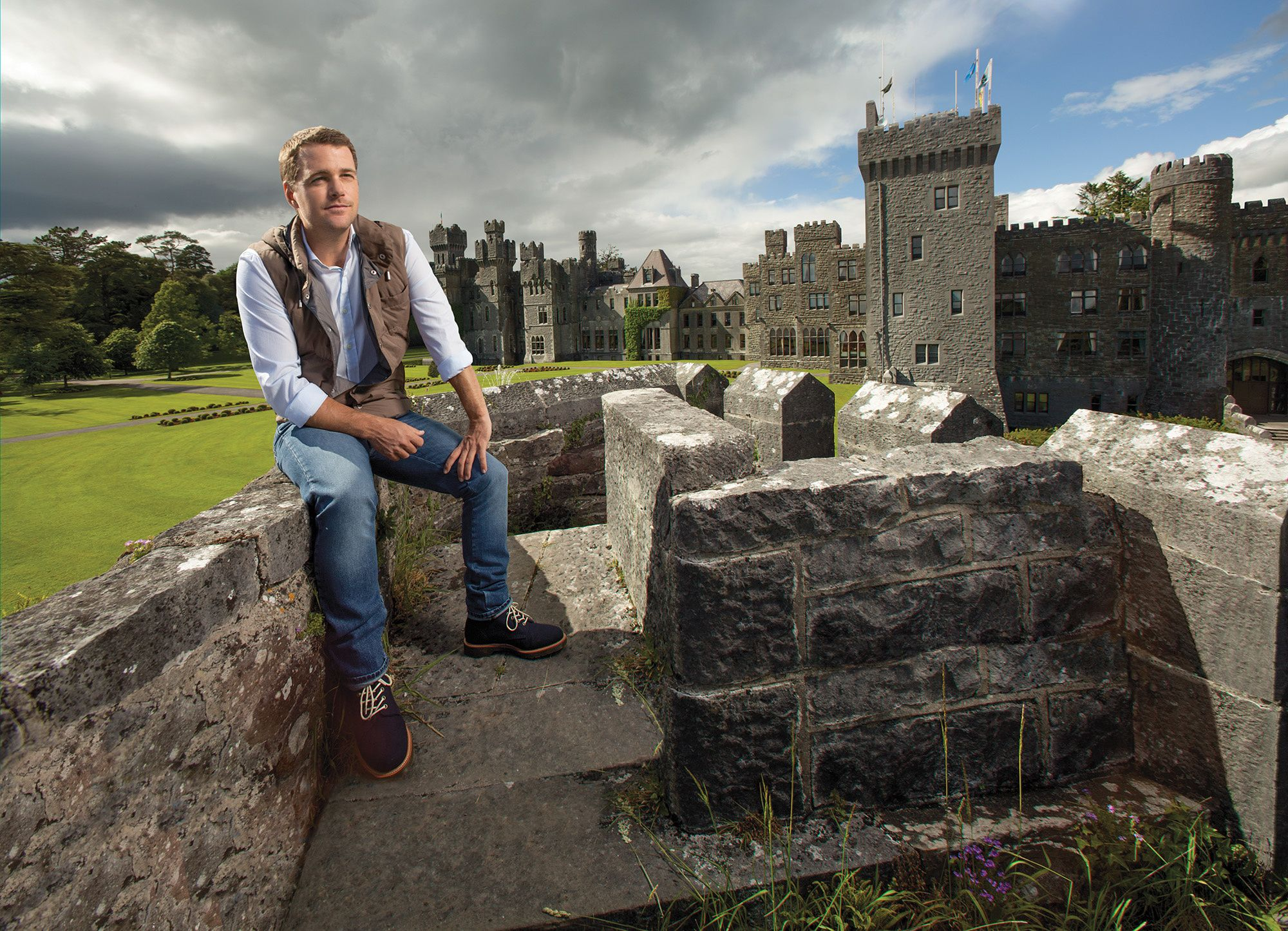 Chris O'Donnell sitting on stone wall with Ashford Castle behind him.