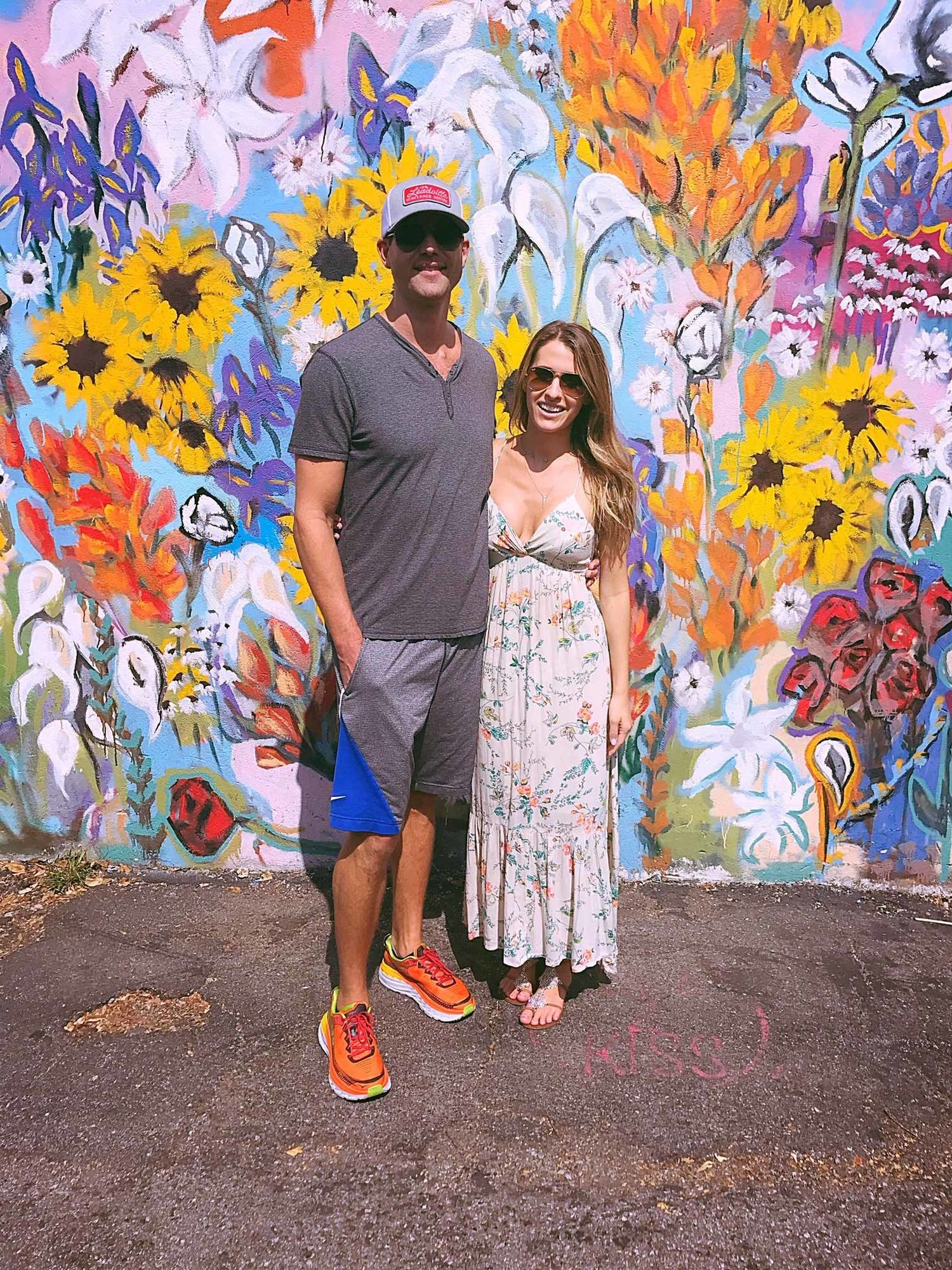 Dr. Travis Stork and his wife in front of a mural in Nashville.